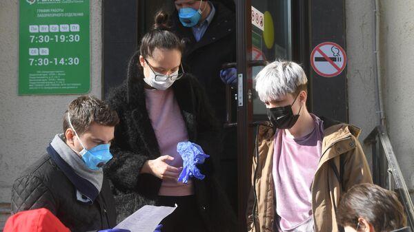 Молодые люди в защитных масках у входа в медицинскую лабораторию Гемотест в Москве