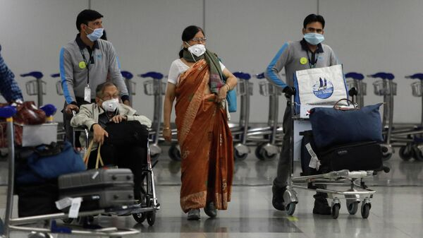 Персонал аэропорта сопровождает пожилых людей после вспышки коронавируса в Нью-Дели, Индия