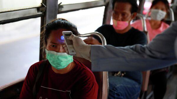 Проверка температуры тела у пассажира на КПП в Бангкоке в связи со вспышкой коронавируса в Таиланде