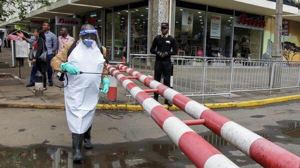 Рабочий распыляет дезинфицирующее средство по улицам Кении