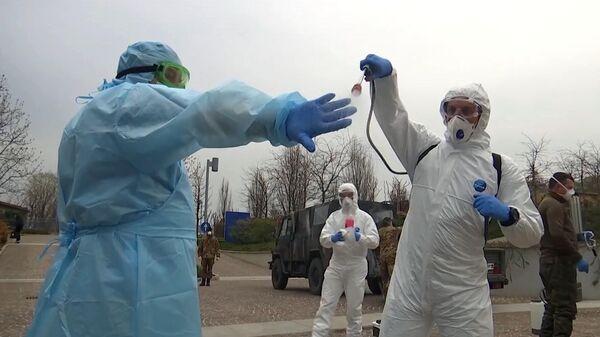 Российские военные специалисты в костюмах бактериологической защиты на территории лечебного учреждения в Бергамо, Италия