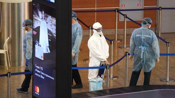 Медики в защитных костюмах в зоне прилета в аэропорту Шереметьево