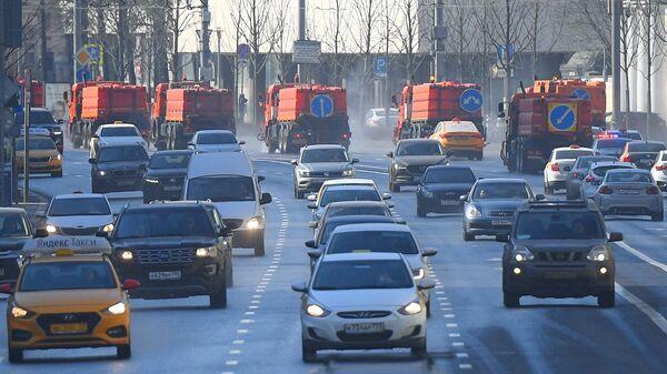 На дальнем плане - автомобили коммунальной службы производят мытье асфальтового покрытия с использованием специального моющего средства в Москве