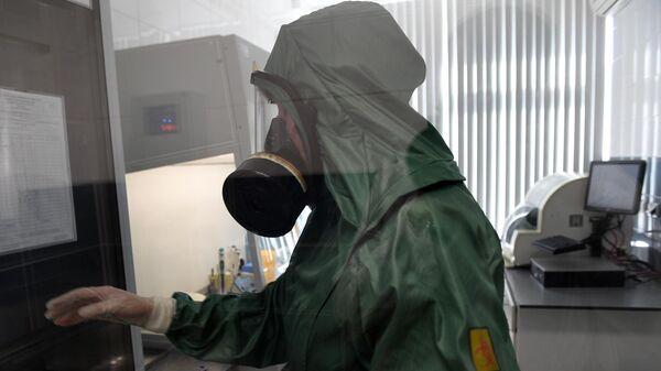 Сотрудник в костюме биозащиты за работой в вирусологической лаборатории, где производится анализ на новую коронавирусную инфекцию