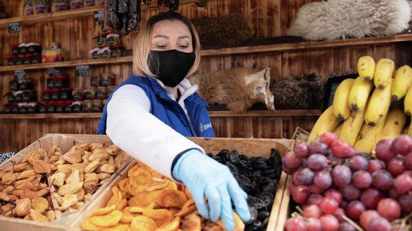 Продавец в защитной маске изображен на курорте Красная Поляна в Сочи, Россия