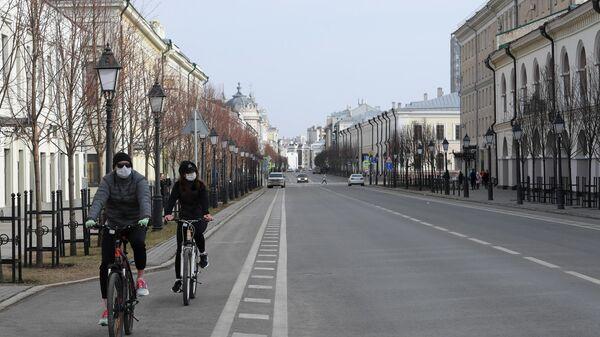 Велосипедисты в защитных медицинских масках на пустынной улице в Казани