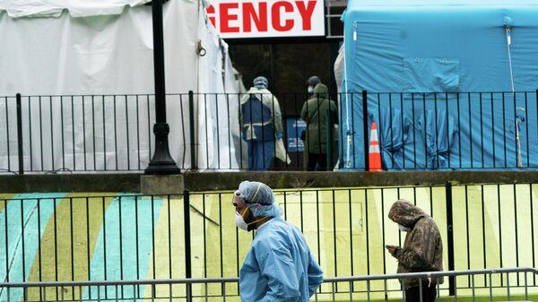 Медики и пациенты у больничного центра Elmhurst в районе Квинс, Нью-Йорк