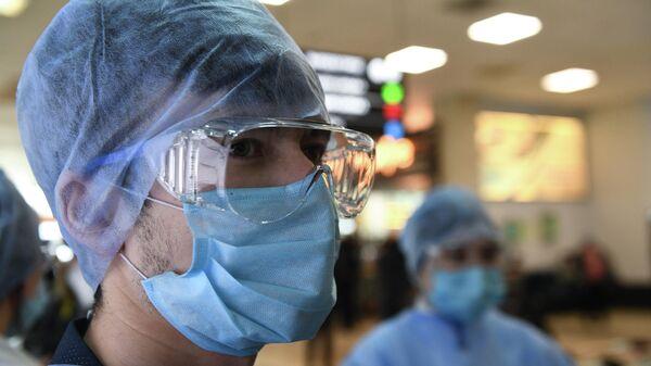 Волонтеры и студенты Новосибирского медицинского колледжа контролируют прибывающих пассажиров в аэропорту Толмачево в Новосибирске