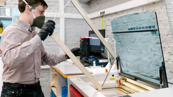 Сотрудник технопарка Кванториум. Новатория в Иваново во время производства лицевого экрана для индивидуальной защиты глаз, дыхательных путей и лица медицинских работников