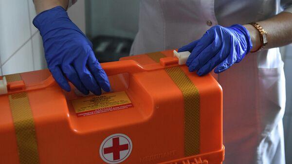 Чемодан с лекарственными средствами в руках у врача на подстанции скорой помощи