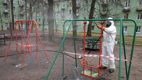 Сотрудник коммунальной службы проводит дезинфекцию на детской площадк