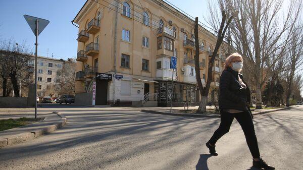 Женщина в медицинской маске на одной из улиц в Волгограде
