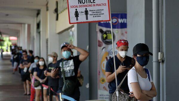 Местные жители в защитных масках на улице Манилы, Филиппины