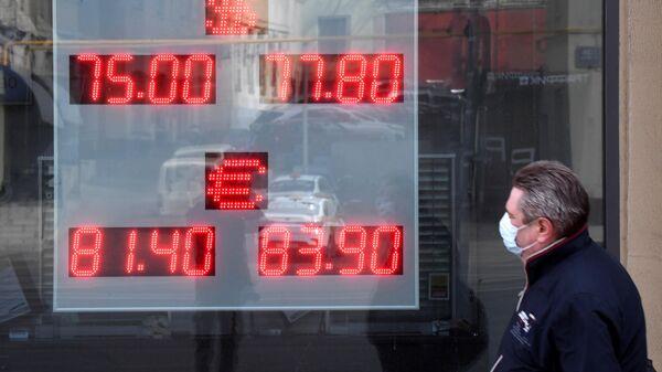 Мужчина в медицинской маске у информационного табло с курсом валют на улице Земляной Вал