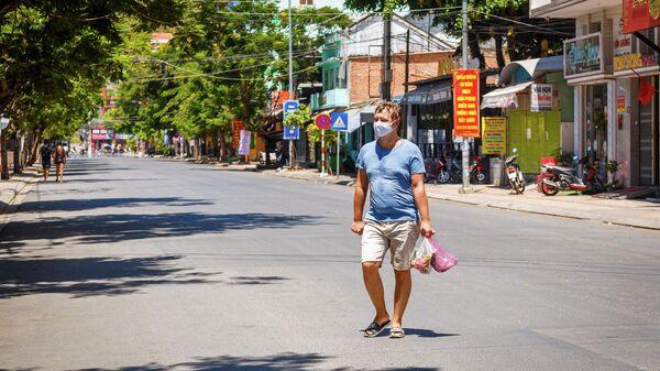 Турист в защитной маске в курортном городе Нячанг во Вьетнаме