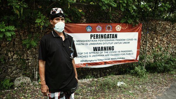 Местный житель в защитной маске в поселке Джимбаран на острове Бали в Индонезии