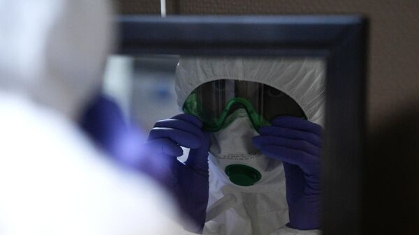 Сотрудник клинической больницы РЖД-Медицина им. Н. А. Семашко в Москве одевает защитный костюм