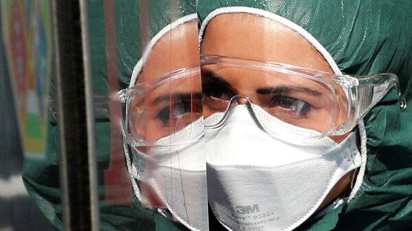 Медицинский работник в защитном костюме в больнице для пациентов с коронавирусом в Риме
