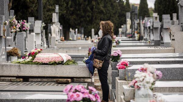 Женщина стоит у могилы матери, умершей от коронавируса, на кладбище Альмудена в Мадриде