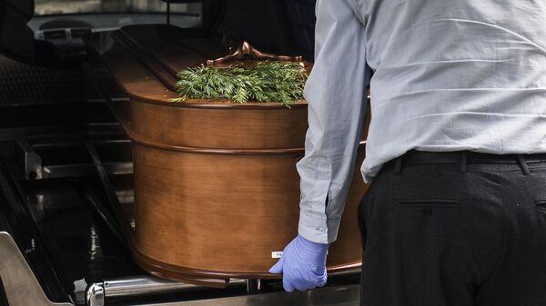 Грузчик достает гроб из катафалка на кладбище Альмудена в Мадриде