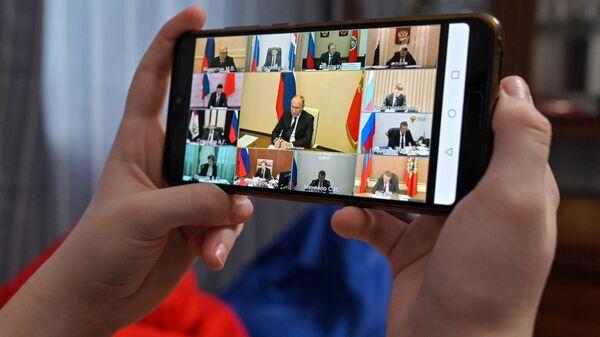 Житель Москвы смотрит трансляцию совещания президента РФ Владимира Путина с руководителями субъектов РФ