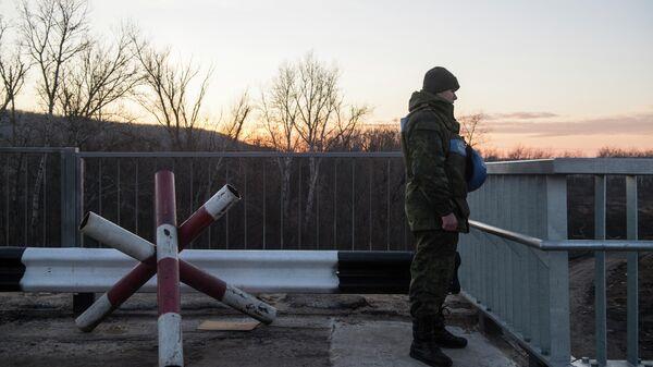 Сотрудник СЦКК на контрольно-пропускном пункте  Станица Луганская