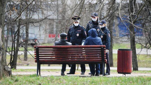 Сотрудники полиции разговаривают с людьми, сидящими на скамейке в сквере