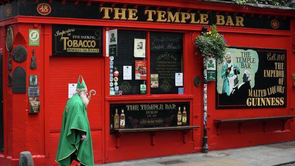 Мужчина в костюме Святого Патрика проходит мимо паба в Дублине