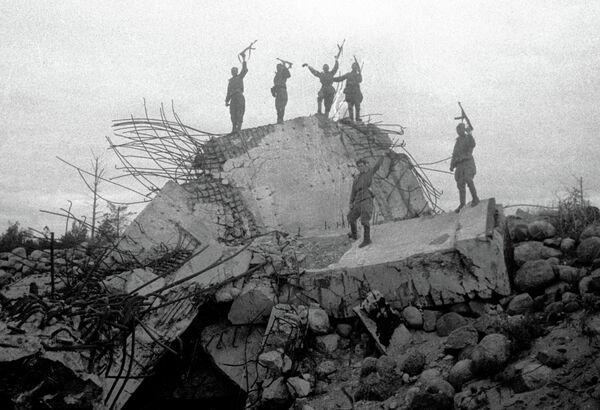 Красноармейцы стоят на обломках одного из немецких дотов, взорванных советскими войсками