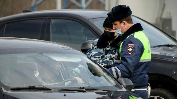 Сотрудники дорожно-патрульной службы ГИБДД проверяют документы у водителя на блокпосту при въезде в Москву на пересечении с МКАД