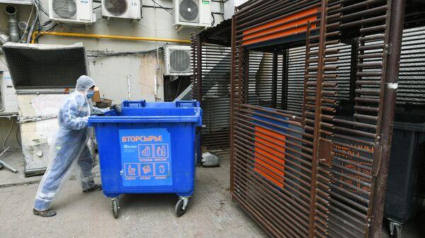Сотрудник компании Эколайн устанавливает на место мусорный контейнер после выгрузки его содержимого в мусоровоз в одном из дворов Москвы