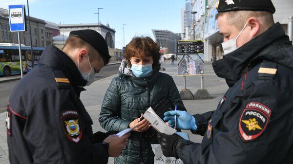 Сотрудники полиции проверяют цифровой пропуск у женщины в Москве