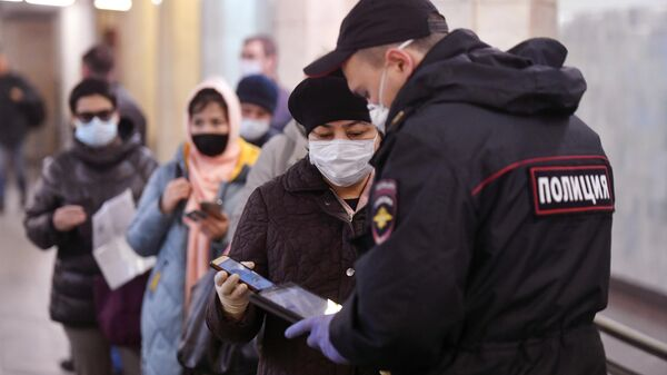 Пассажирка метро показывает код своего электронного пропуска на экране смартфона сотруднику полиции на станции метро Сокольники в Москве