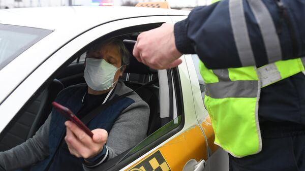 Сотрудник дорожно-патрульной службы ГИБДД во время проверки электронного пропуска у водителя такси на блокпосту при въезде в Москву