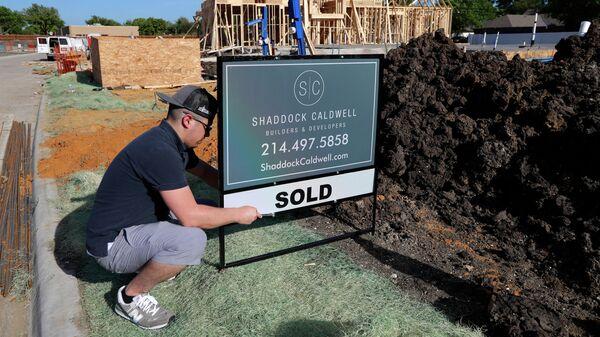 Мужчина устанавливает табличку с объявлением о продаже дома в штате Техас