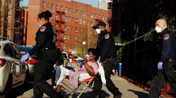 Сотрудники неотложной медицинской помощи Департамента пожарной охраны Нью-Йорка перевозят пациента
