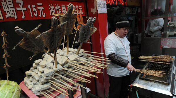 Продавец в киоске экзотической еды на торговой улице Ванфуцзин в Пекине