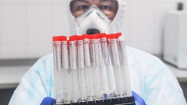 Лаборант держит в руках пробирки с биоматериалом для тестирования на коронавирусную инфекцию