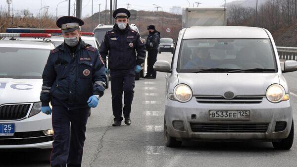 Инспекторы ДПС проверяют документы у водителей, въезжающих на остров Русский