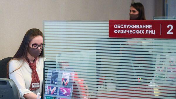 Сотрудница банка в защитной маске во время приема посетителей в отделении Московского кредитного банка