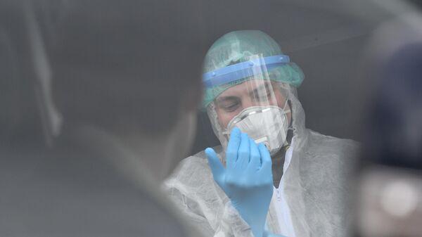 Сотрудник клиники Чайка проводит забор биоматериала для анализа на коронавирус у жителя Москвы в его машине