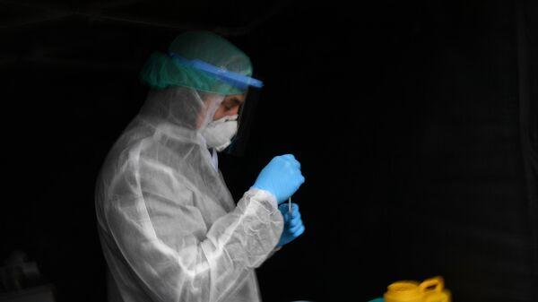 Сотрудник клиники Чайка в защитном костюме