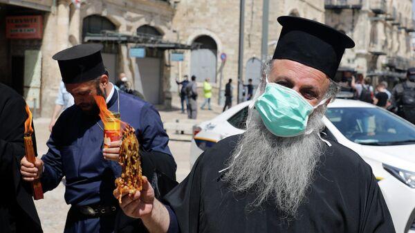 Греческий православный священник  держит зажженные от Святого Огня в храме Гроба Господня свечи