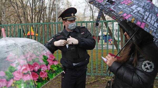 Сотрудник полиции проверяет цифровой пропуск у прохожих в Москве