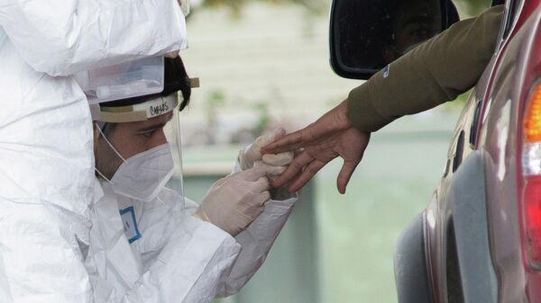 Медицинский работник берет анализ для тестирование на коронавирус в Болинасе, США