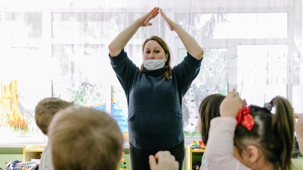 Воспитатель в медицинской маске играет с детьми в детском саду