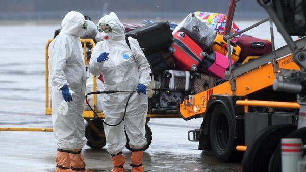 Сотрудники Роспотребназора Республики Татарстан обрабатывают антисептическим средством багаж пассажиров