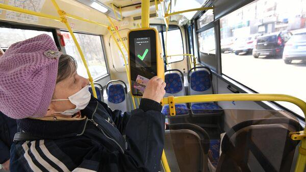 Женщина в защитной маске прикладывает социальную карту москвича к валидатору в салоне городского автобуса в Москве