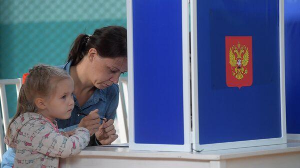 Девушка голосует на выборах