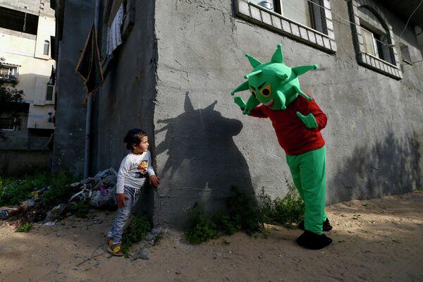 Палестинец, одетый в костюм коронавируса играет с девочкой в центральной части Сектора Газа